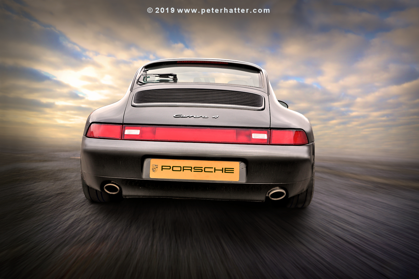 An image of a Porsche 911 Carrera rear view.