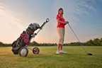 Female golfer with driver and bag on the fairway